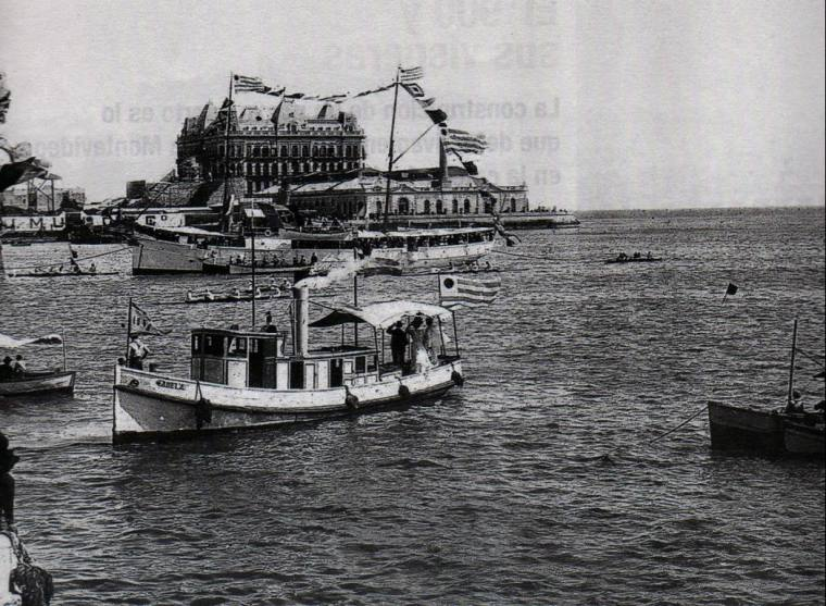 Races organized by the Montevideo Rowing Club in Montevideo Bay. The Hotel Nacional, in the background, was one of the greatest schemes of the National Company of Credit and Public Works. Victim of the 1890 crisis, the building  was never operational, and the French manager stayed some years in the empty hotel waiting for an inauguration that never happened.