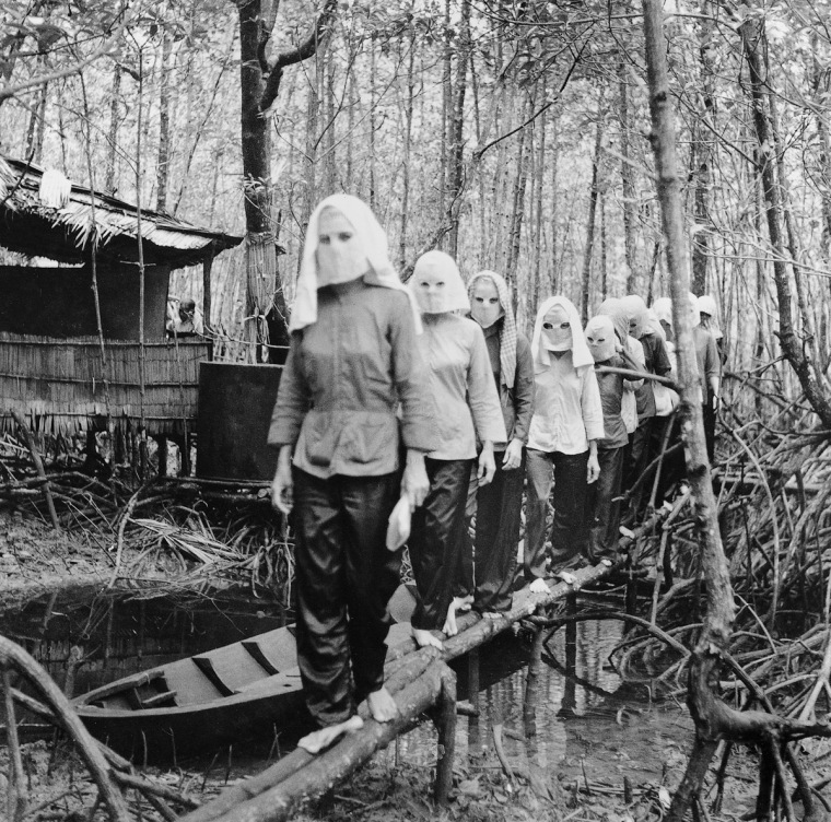 Activists meet in the Nam Can forest, wearing masks to hide their identities from one another in case of capture and interrogation.  IMAGE: VO ANH KHANH/ANOTHER VIETNAM/NATIONAL GEOGRAPHIC BOOKS